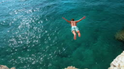 COPY SPACE: Man jumping off a rocky ledge and into the glistening blue ocean.