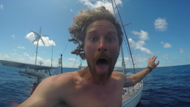 stockvideo's en b-roll-footage met a man jumping off a sailboat boat and swimming in the pacific ocean. - slow motion - ontdekkingsreiziger