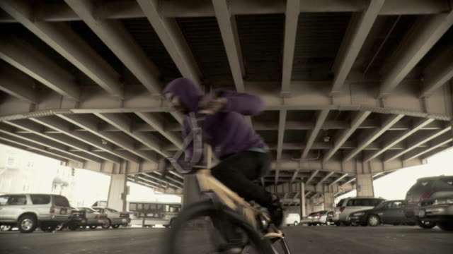 ms ds la slo mo man jumping on bmx bicycle under overpass, brooklyn, new york city, new york state, usa - hooded top stock videos & royalty-free footage