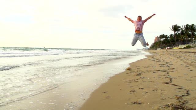 vídeos y material grabado en eventos de stock de hd super cámara lenta: salto de hombre en la playa de florida - miembro humano