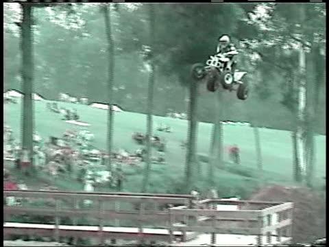 ms, pan, zo, composite,  man jumping on quad bike across foot bridge and crashing, paramedics taping man's broken arm, usa - film composite stock videos & royalty-free footage
