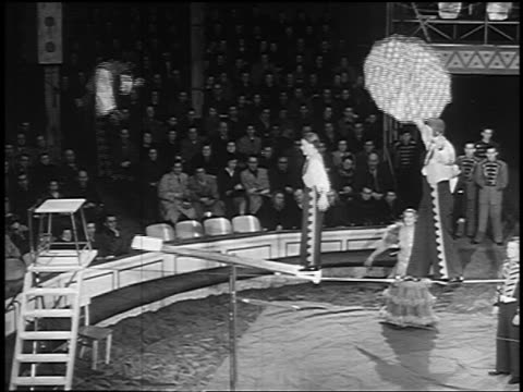 B/W 1955 man jumping on seesaw bouncing woman who flips + lands on shoulders of man on tightrope