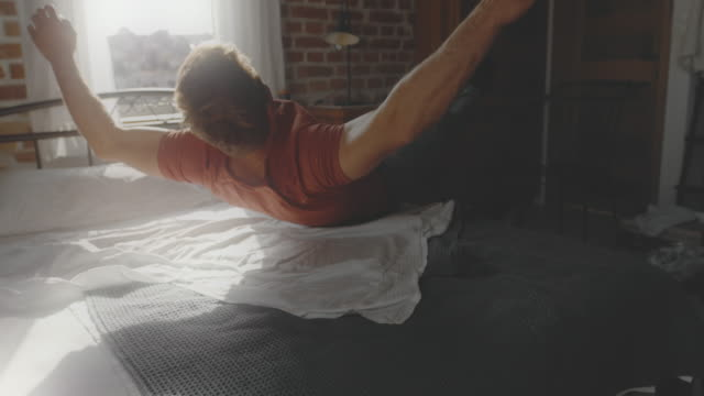 slo mo man jumping on the bed - riposarsi video stock e b–roll