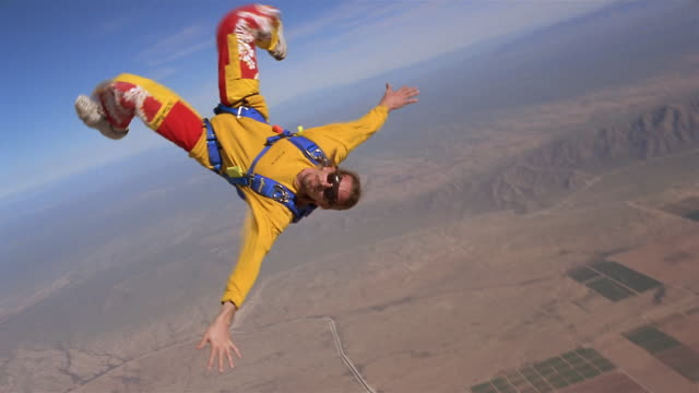 ws man jumping out of private airplane with parachute and floating upside down in mid air above patchwork landscape / eloy, arizona, usa - patchwork landscape stock videos and b-roll footage