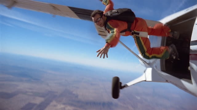 ws man jumping out of private airplane with parachute in mid air above patchwork landscape / eloy, arizona, usa - jumping stock videos & royalty-free footage