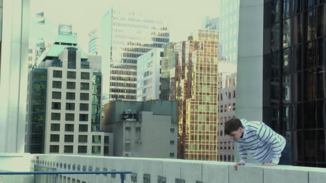 MS Man jumping over building ledge and running away, performing parkour, Vancouver, British Columbia, Canada