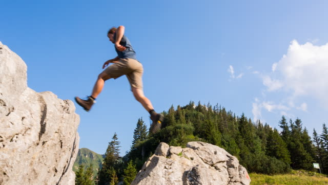 man jumping over gap in mountain boulder - boulder rock stock videos & royalty-free footage