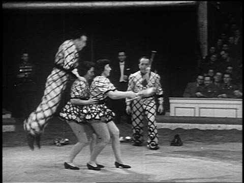 b/w 1955 man jumping over two women juggling pins in circus / man starts juggling after jumping - jonglieren stock-videos und b-roll-filmmaterial