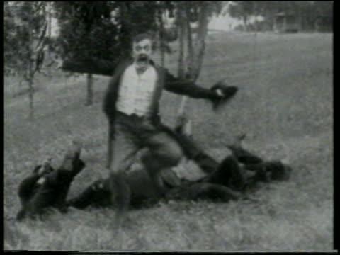 b/w 1915 man jumping + running away from something offscreen past keystone kops lying in grass - 1915年点の映像素材/bロール