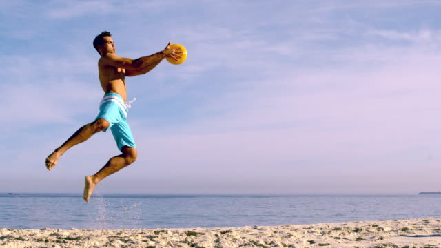man jumping to catch a frisbee - solo uomini giovani video stock e b–roll