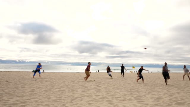 ws man jumping to catch pass during touch football game on beach - touch football video stock e b–roll