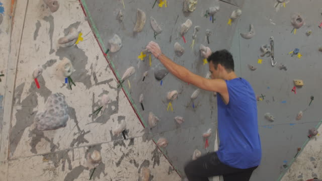 man jumping to reach a boulder at the climbing wall - reaching stock videos & royalty-free footage