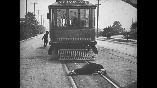 1921 man (buster keaton) jumps in front of a trolley in an attempt to commit suicide, but the trolley stops and reverses it's route just before hitting him - 1921年点の映像素材/bロール