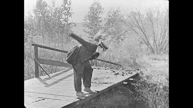 1921 man (buster keaton) jumps on a bridge expecting his horse to walk underneath and is surprised when he sits down on a wild bull instead of his horse - 1921年点の映像素材/bロール