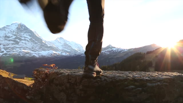 Man jumps onto a boulder to admire the mountain sunset