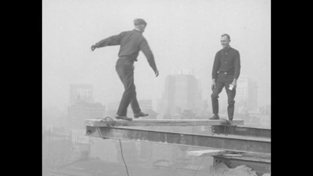 man jumps rope on a girder high above manhattan and is seen from far below; he is blindfolded, walks along and almost falls; good shots of him doing... - 桁橋点の映像素材/bロール