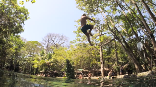 man jumps to the water with a liana. low point of view. a wave goes to camera. natural swimming pool of ojo de agua. ometepe, nicaragua. - vine stock videos and b-roll footage
