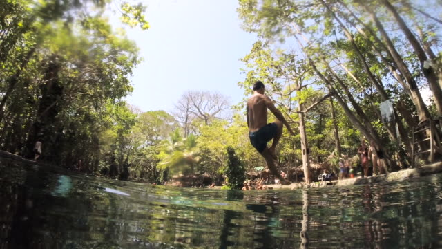 man jumps to the water with a liana. low point of view. a wave goes to camera. natural swimming pool of ojo de agua. ometepe, nicaragua. - agua stock-videos und b-roll-filmmaterial