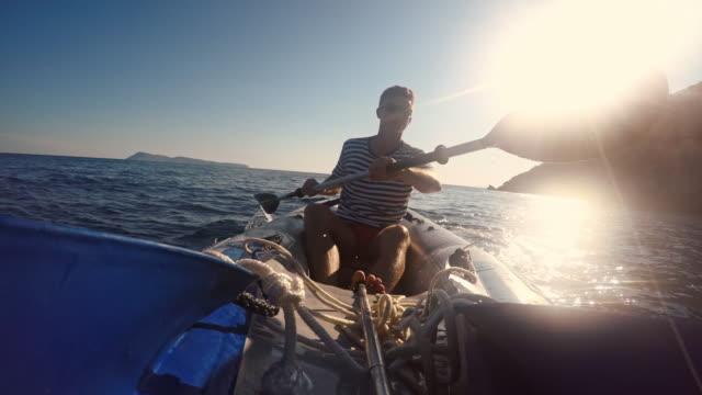 vidéos et rushes de homme en kayak le long de la côte - pagayer
