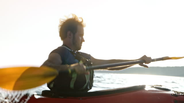 slo mo ts man kayaking at sea in sunshine - kayak stock videos & royalty-free footage