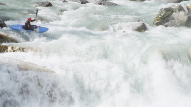 MS Man kayaking between rocks in white water rapids