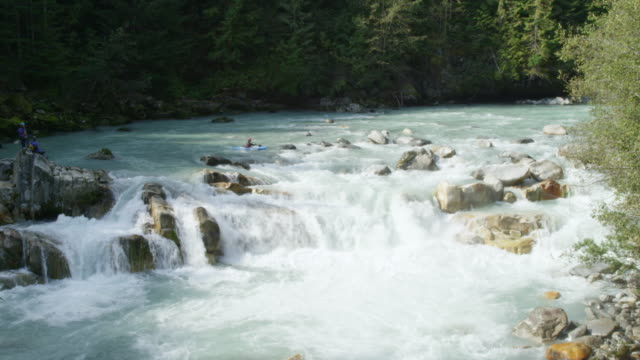 MS Man kayaking off waterfall in white water rapids with friends watching in the distance