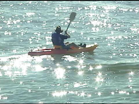 vídeos de stock, filmes e b-roll de homem andando de caiaque no lago porto de vídeo - artigo de vestuário para cabeça