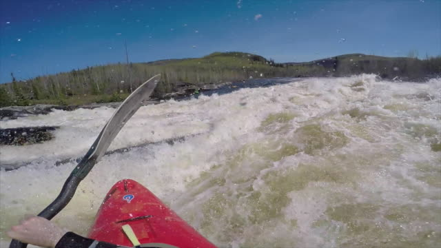 A man kayaks down a waterfall on a river. - Slow Motion