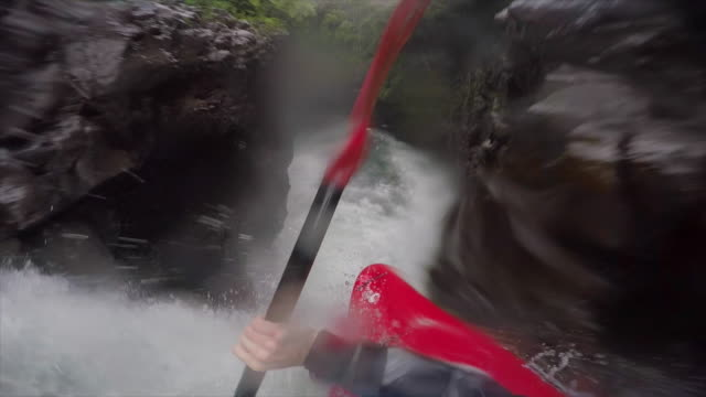 A man kayaks down a waterfall on a river.