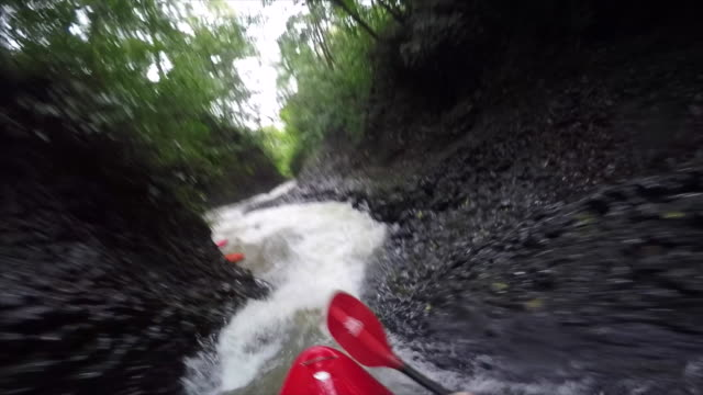 a man kayaks down a waterfall on a river. - canoe stock videos & royalty-free footage