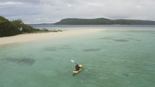 MS A man kayaks next to a tropical island
