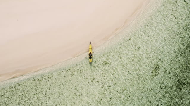 A man kayaks to an empty beach
