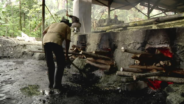 MS Man keeping the fire of the boilers of the sulfur mining / Ijen, Java, Indonesia