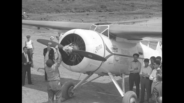 man keeps pushing propeller trying to start motor, people standing around watching / motor running, propeller spinning / closer shot of propeller... - motor video stock e b–roll