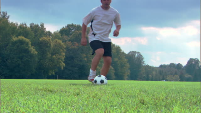 Man kicking soccer ball in field