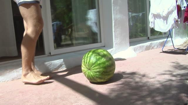 vídeos de stock e filmes b-roll de la man kicking watermelon with heel / cu hole in top of watermelon / ibiza, spain - só homens maduros