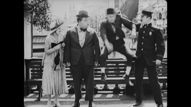 stockvideo's en b-roll-footage met 1917 man (fatty arbuckle) kicks policeman in behind and blames jealous mean man who is taken away by police - verwijten