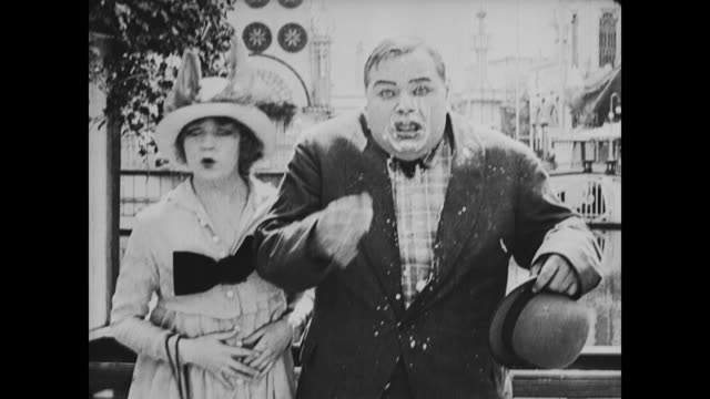1917 man (fatty arbuckle) kicks policeman in rear and blames mean man throwing food - cibi surgelati video stock e b–roll