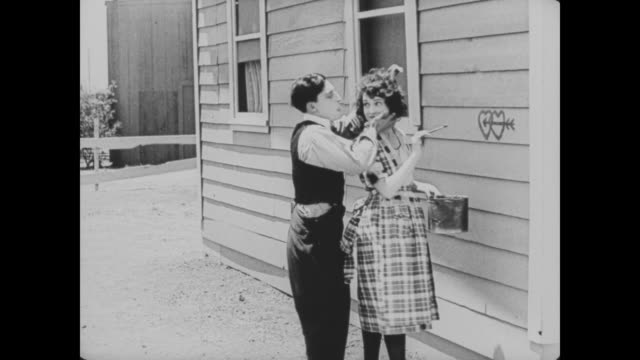 1920 man (buster keaton) kisses his wife (sybil seely) as she paints hearts on the side of the house - 無声映画点の映像素材/bロール