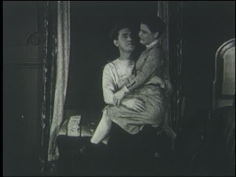 B/W 1920 man kisses woman (Daphne Pollard) sitting on his lap, she slaps him