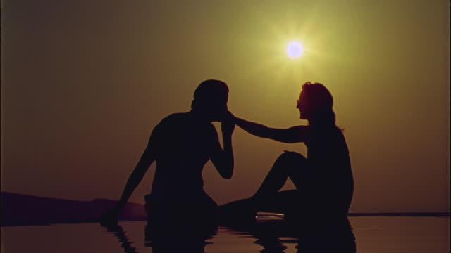 WS Man kissing woman's hand while they sunbathe / Santorini, Greece