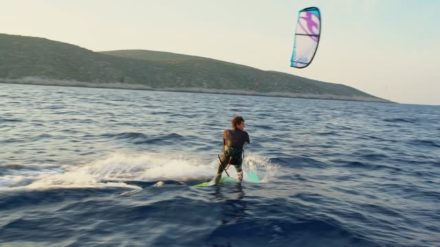 4k man kite sailing on tranquil sunset ocean, real time - kite sailing stock videos and b-roll footage