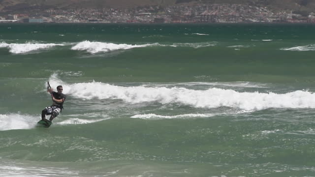 stockvideo's en b-roll-footage met ms pan man kite surfing, container ships in background / cape town. western cape, south africa - voor anker gaan