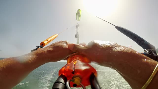 pov man kiteboarding  and jumping into the air in sunshine - kiteboarding stock videos & royalty-free footage