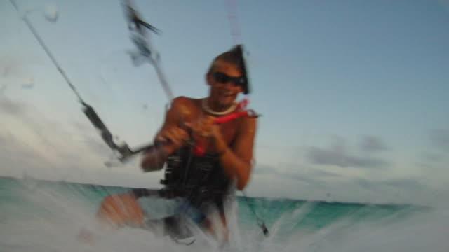 vídeos de stock, filmes e b-roll de la ws pan man kiteboarding in caribbean sea as wave splashes camera / tulum, mexico - tulum méxico