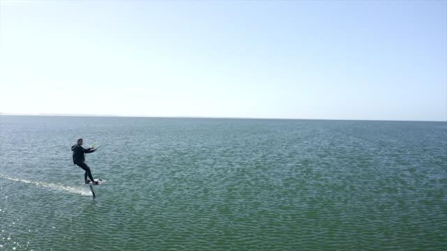 man kiteboarding on a hydrofoil foil on a kite board near a beach. - 4k resolution stock videos & royalty-free footage