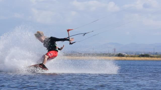 vidéos et rushes de a man kiteboarding on a kite board crashes and fails at landing his trick. - échec