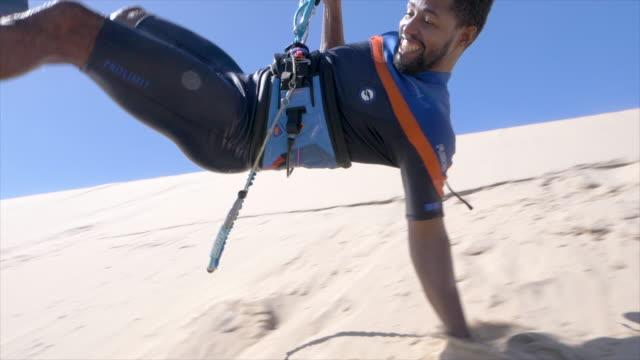 man kiteboarding on a sand dune kite board near a beach. - エクストリームスポーツ点の映像素材/bロール