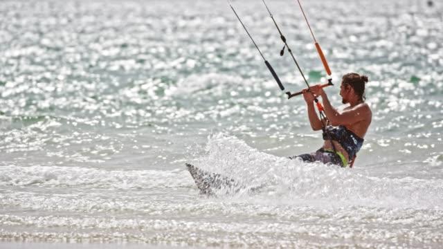 stockvideo's en b-roll-footage met slo mo man kiteboarding op een zonnige dag - sunny