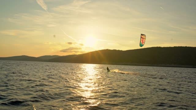 4k man kitesurfing on sunny, tranquil sunset ocean, real time - croatia stock videos & royalty-free footage